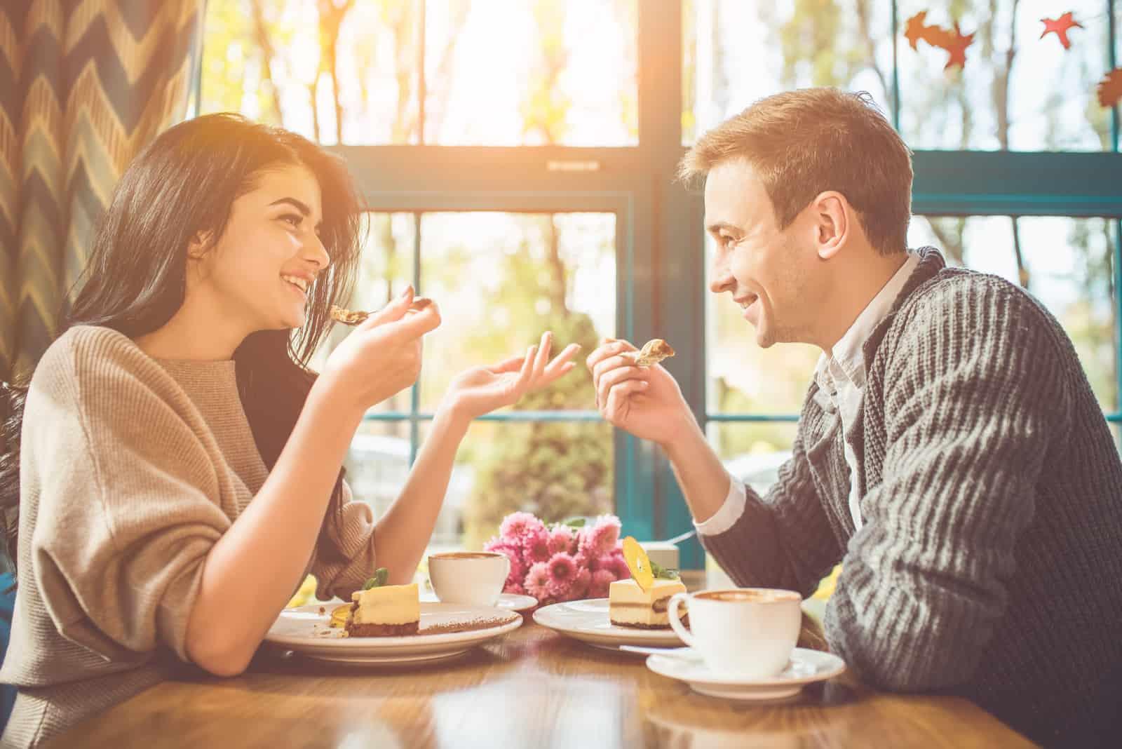 heureux homme femme manger a gâteau dans les café