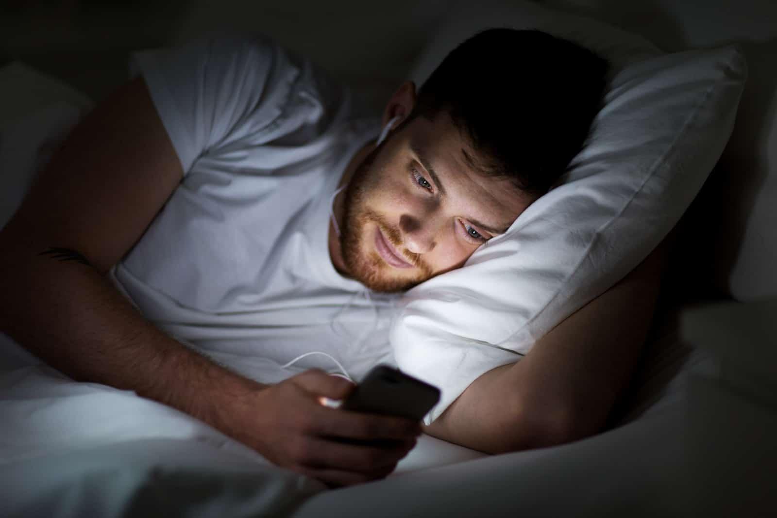 heureux sourire jeune homme à smartphone