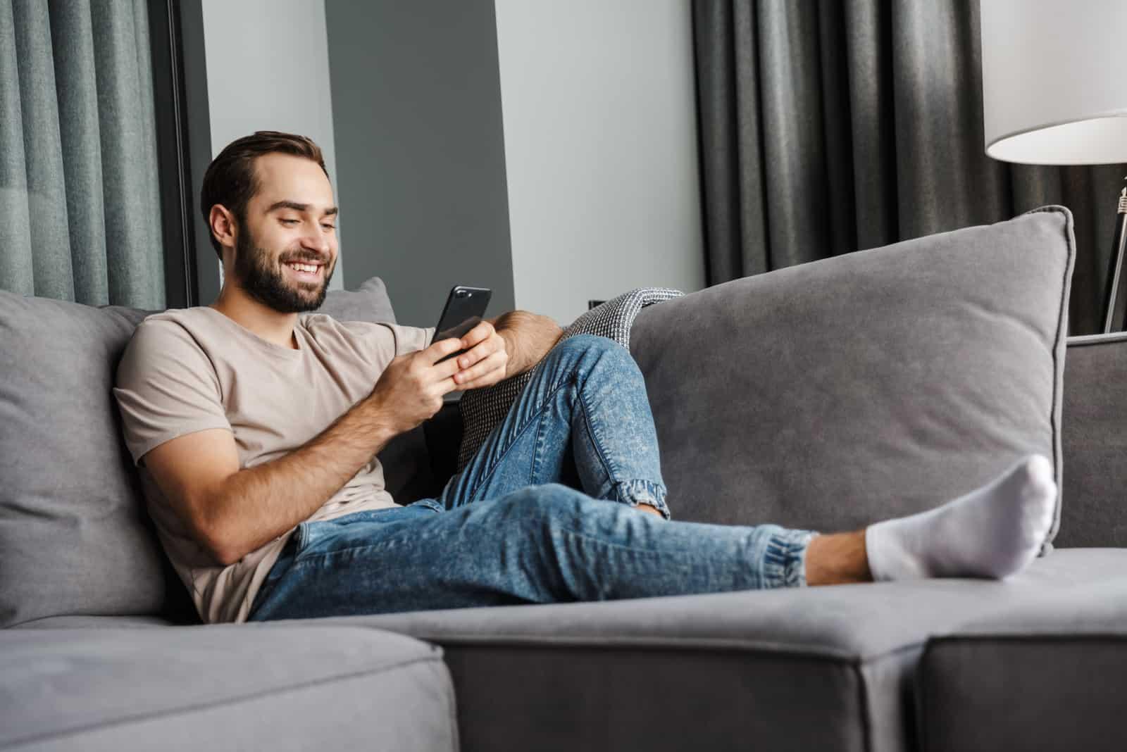 homme à la maison sur un canapé à l'aide de téléphone portable