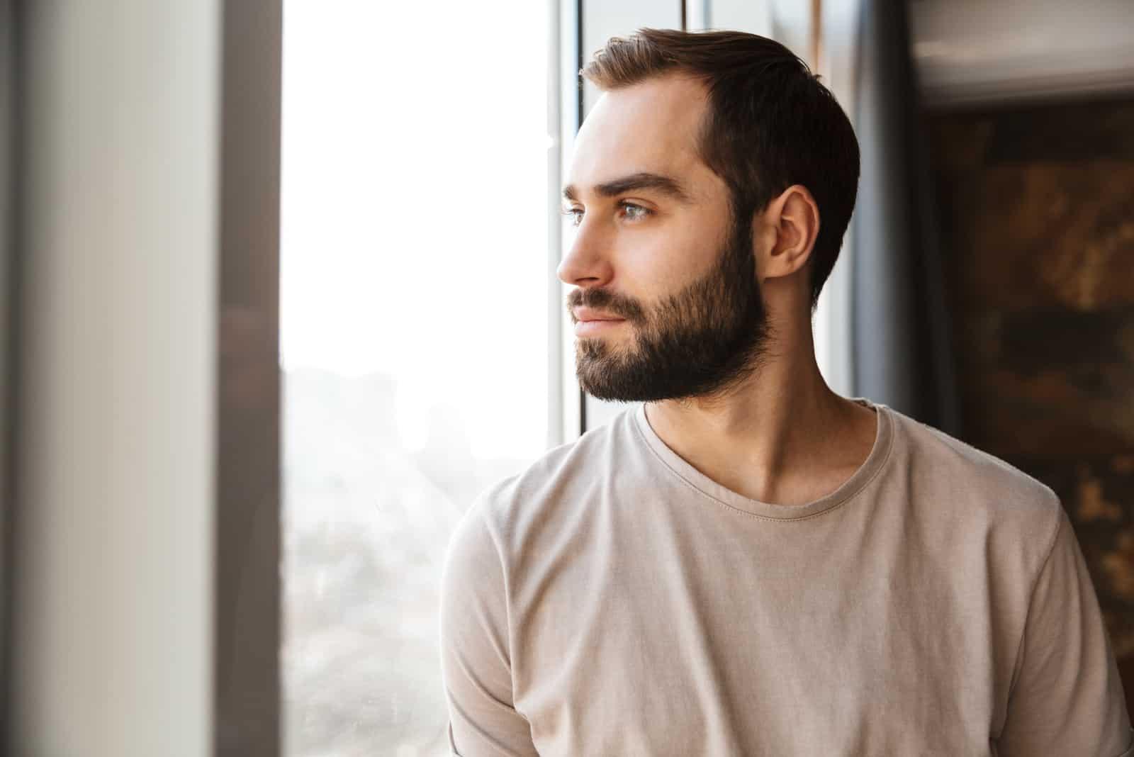 homme barbu debout à la fenêtre à la maison