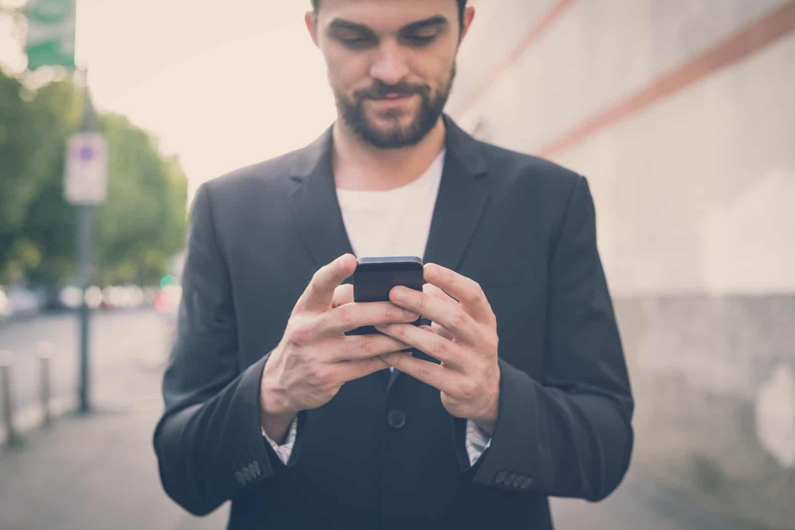 homme moderne hipster à aide de smartphone dans la ville