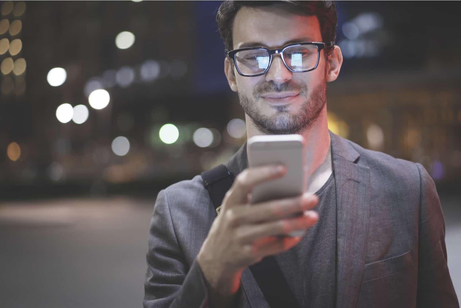homme portant des lunettes tient des textos de défilement dans son téléphone portable