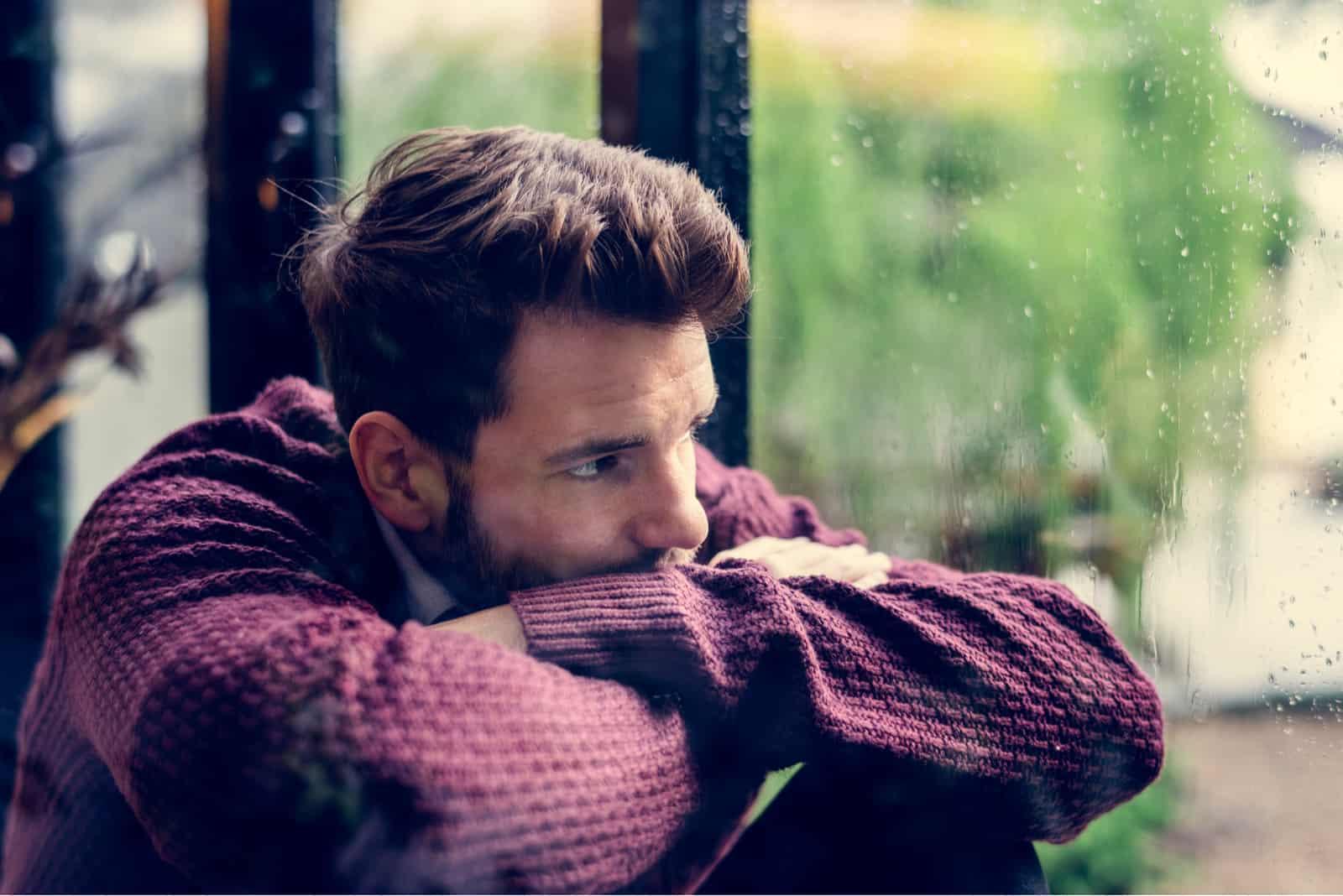 homme réfléchi regardant par la fenêtre