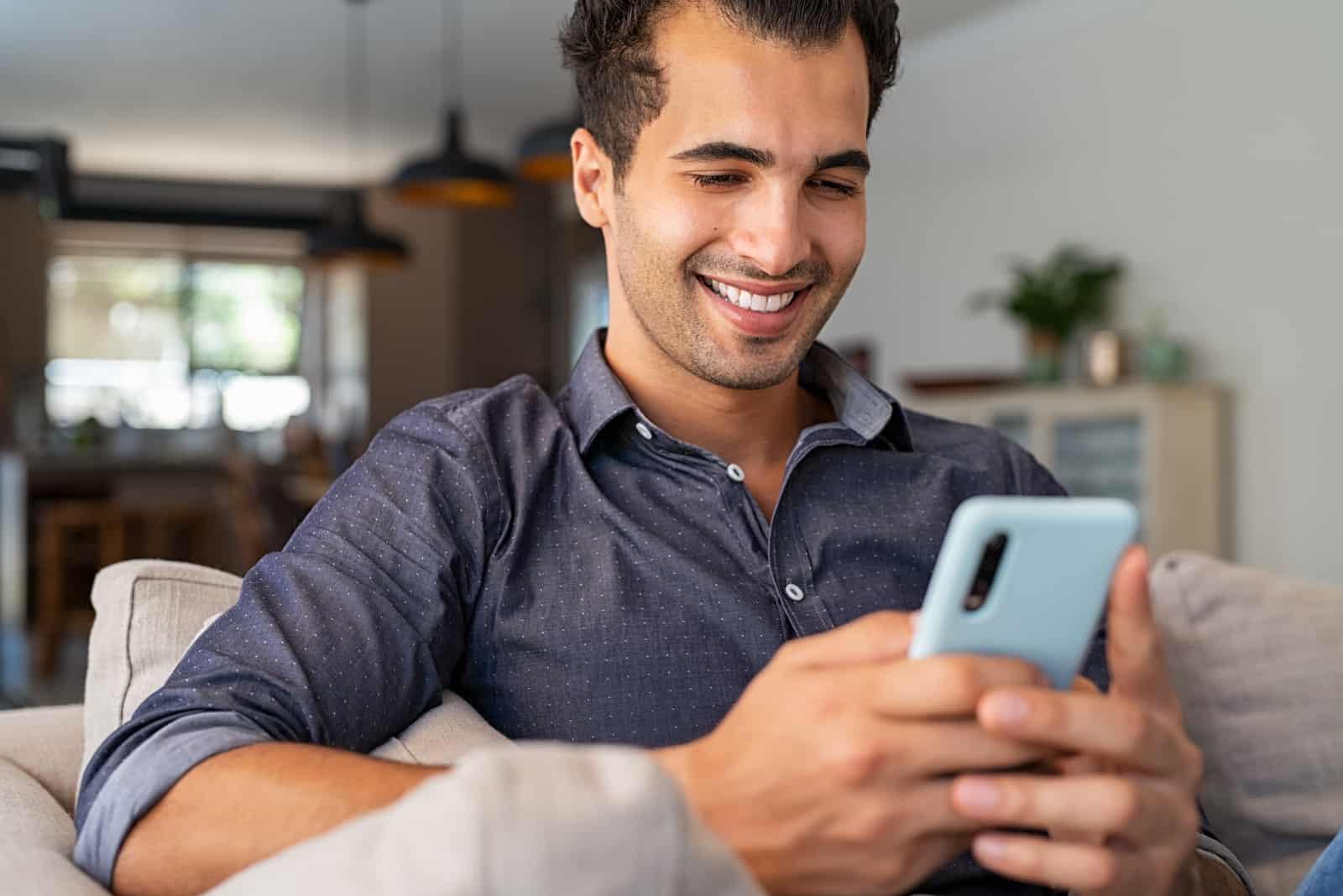 homme souriant, regarde, écran mobile, sur, sofa