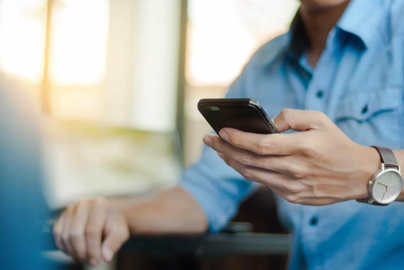 homme sous forme décontractée à l'aide de téléphone mobile