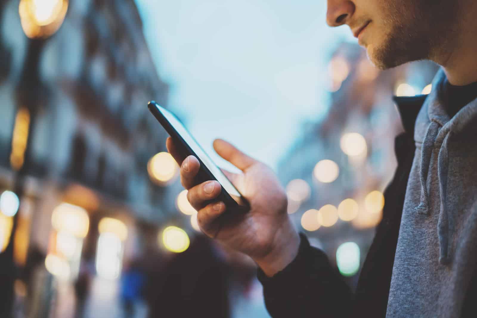 homme utilisant un smartphone dans la rue de la ville de nuit