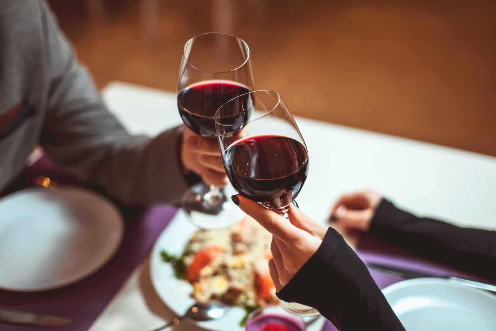 jeune couple avec des verres de vin rouge dans un restaurant de luxe