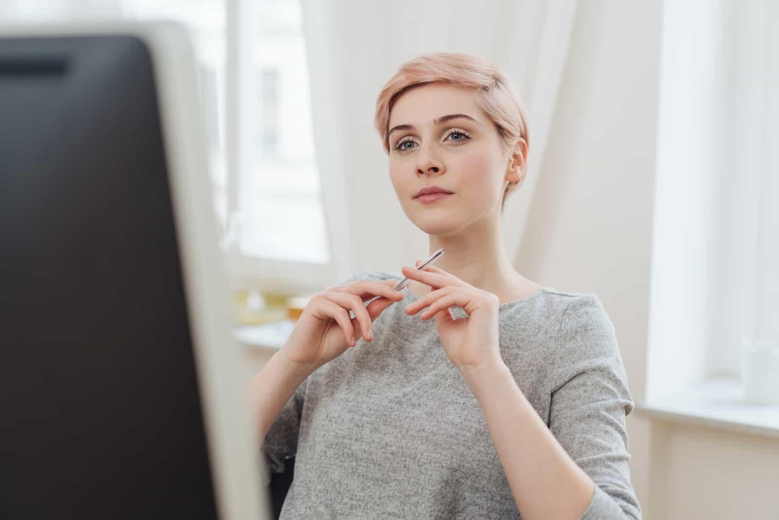 jeune femme assise à un grand écran de bureau