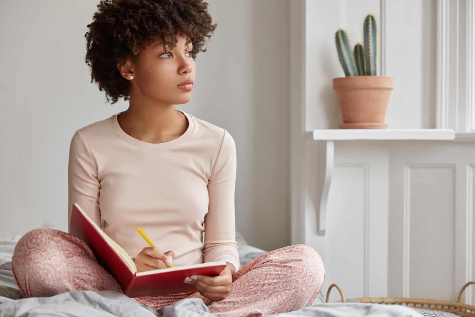 jeune femme assise consciencieusement sur le lit avec ordinateur portable et un stylo