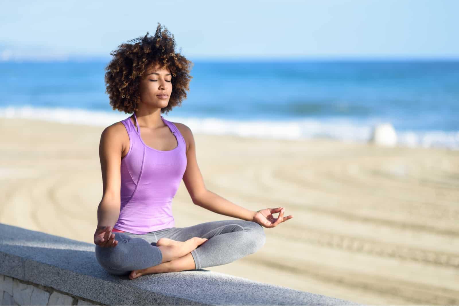 jeune femme médite en plein air au bord de la plage