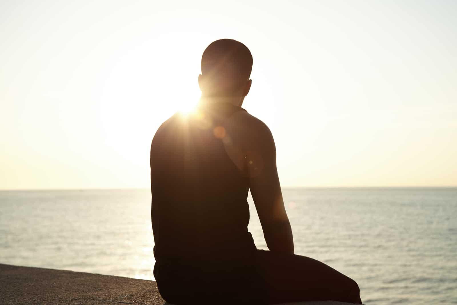 jeune homme assis sur les trottoirs au bord de mer en regardant le soleil