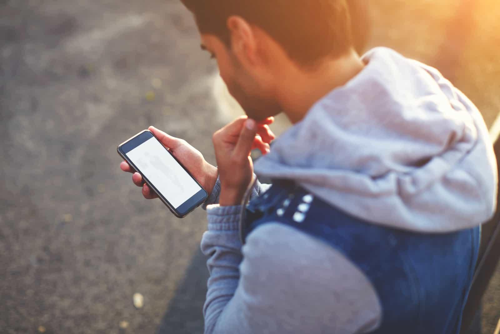 jeune homme, debout, extérieur, et, regarder téléphone portable