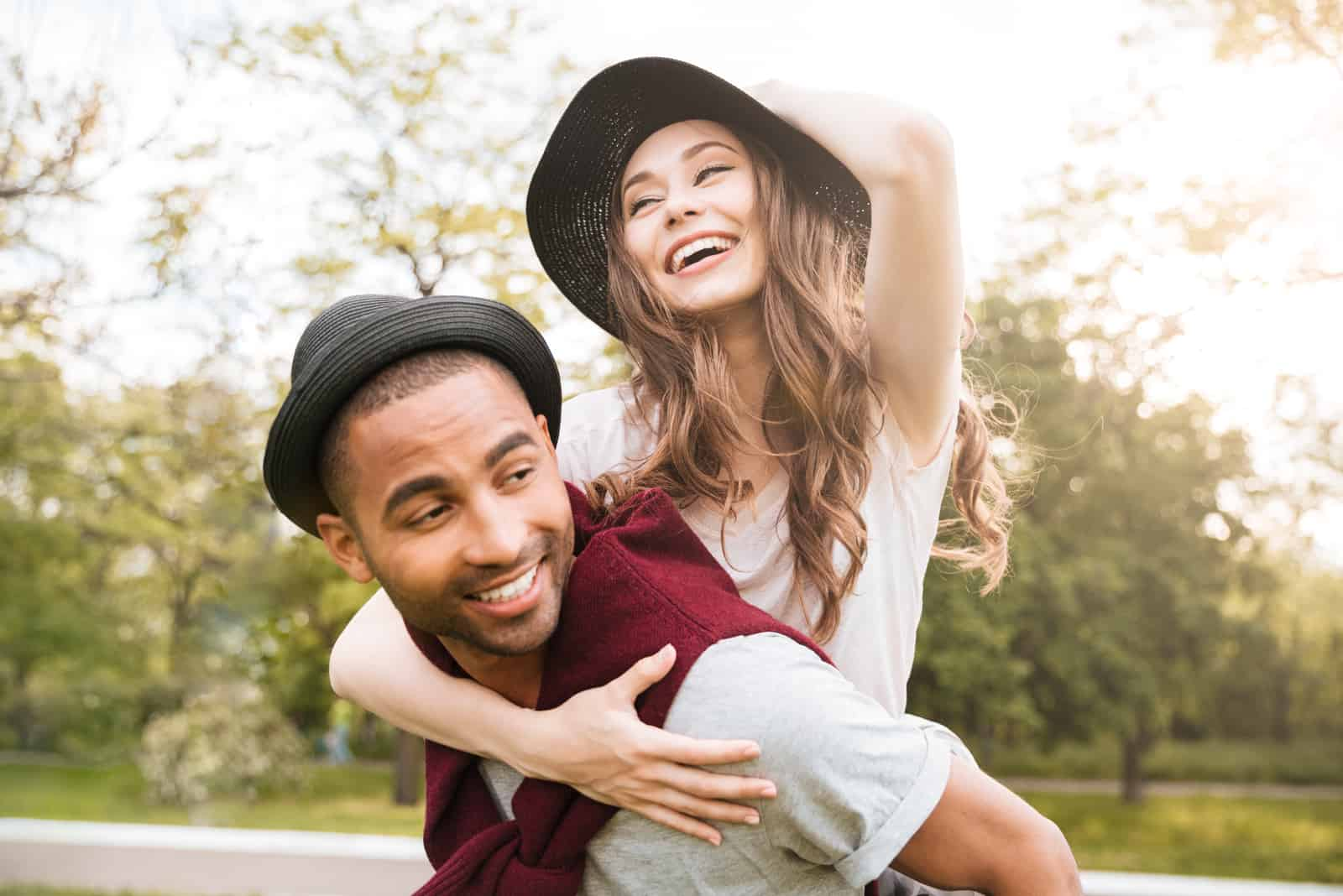 jeune homme porte une femme sur son dos en plein air