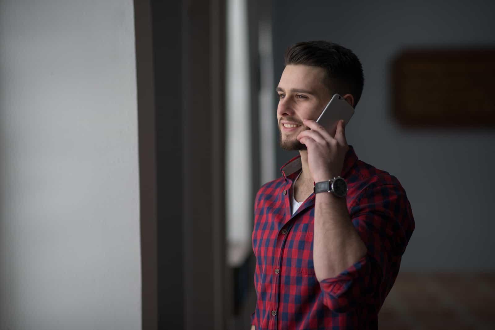 jeune homme souriant tout en parlant au téléphone mobile