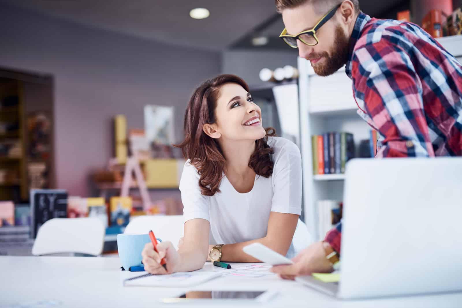 jeune homme travaillant avec une femme souriante au bureau