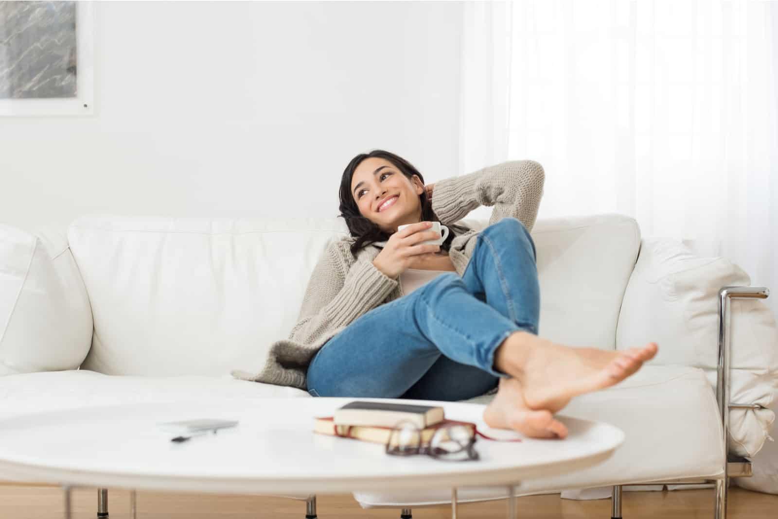 la femme est allongée sur le canapé et rit