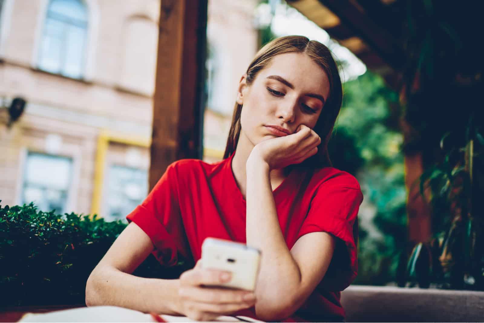 la femme imaginaire s'assied et tient le téléphone dans sa main