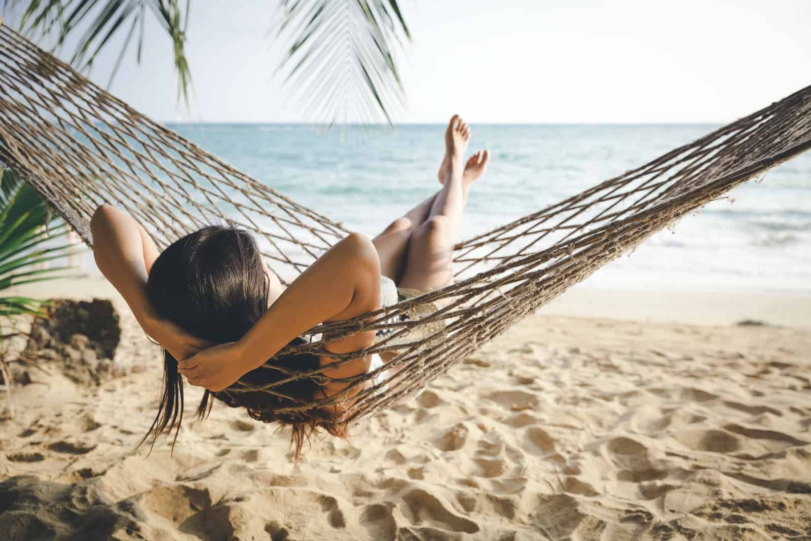 la femme jouit de la vue sur la mer alors qu'elle se trouve dans la chaise longue