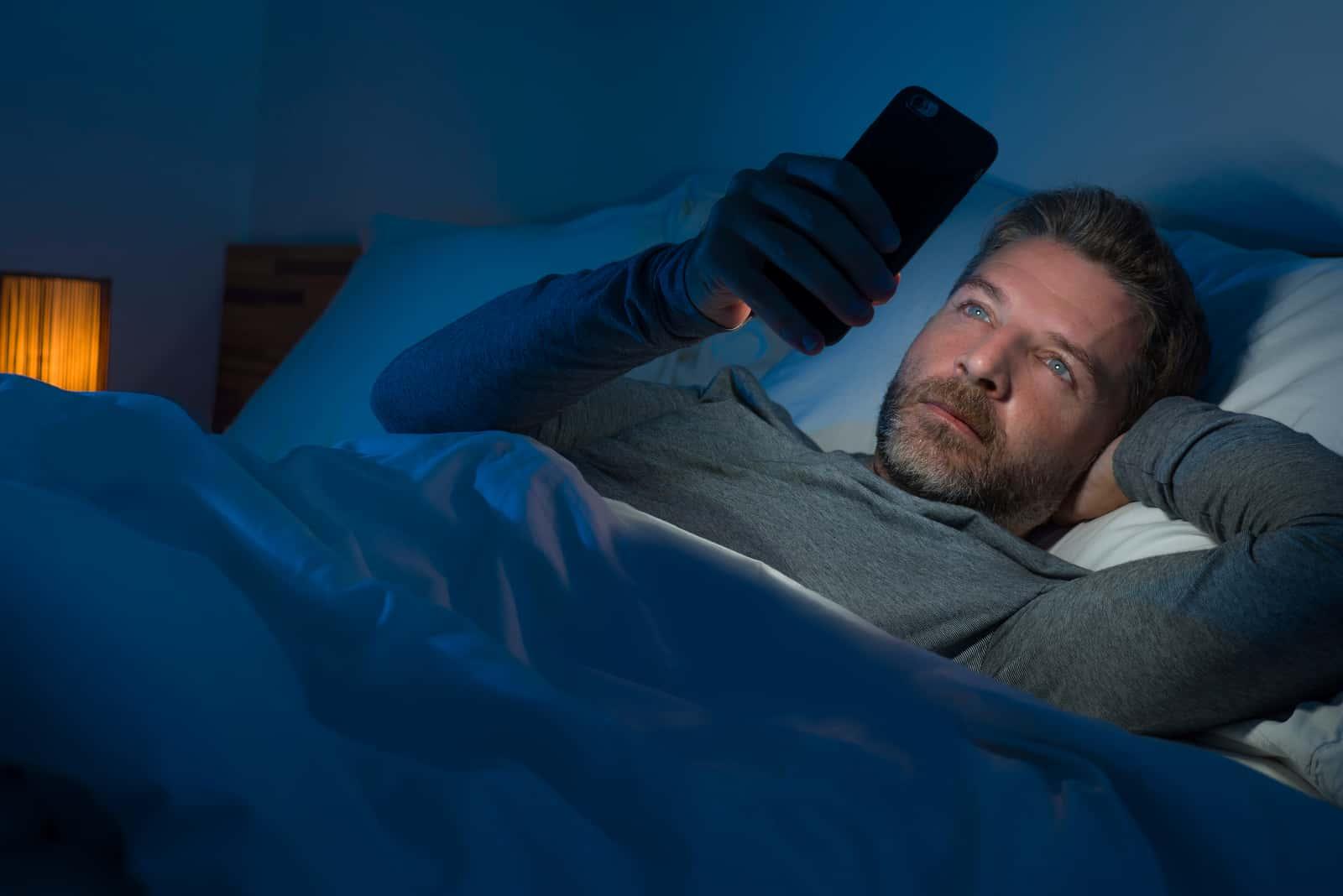 l'homme est allongé dans son lit et tient un téléphone à la main