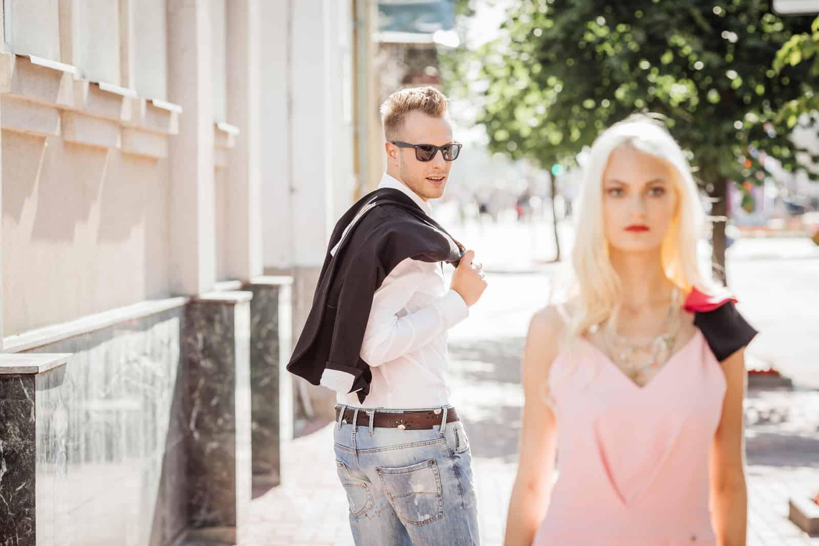 l'homme se tourne vers la femme en marchant dans la rue