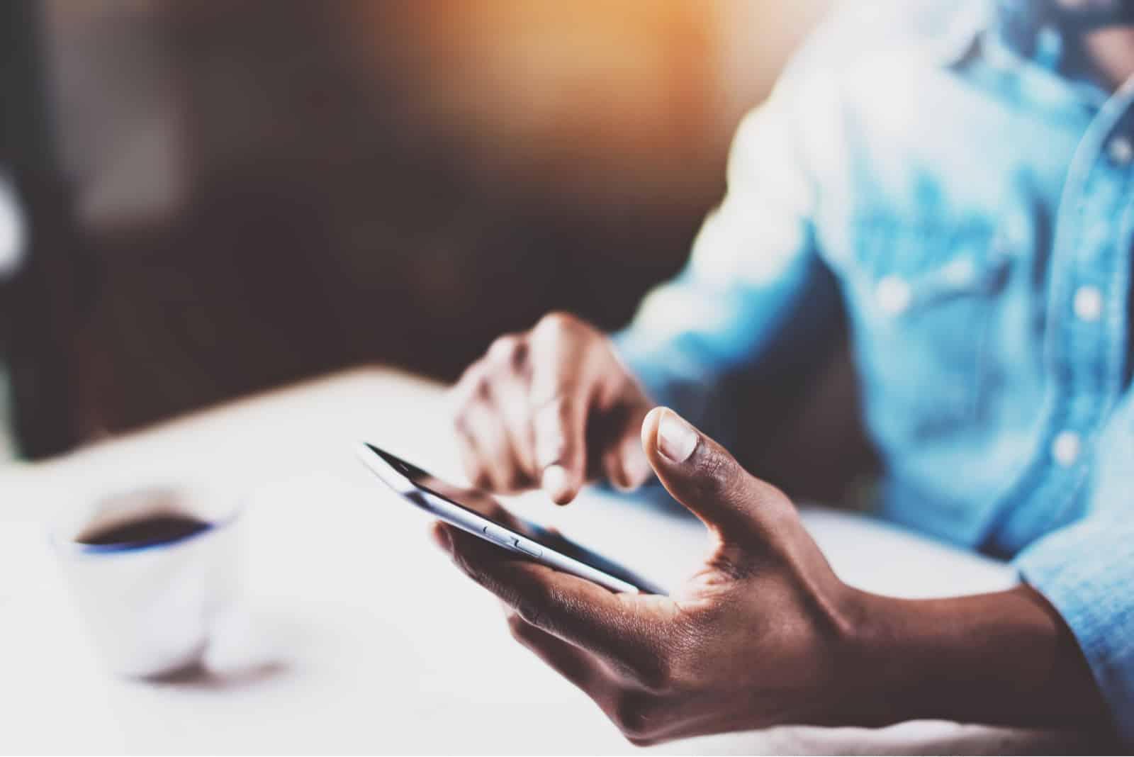 mains mâles touchant le téléphone mobile