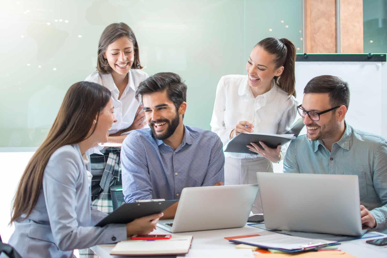 souriant collègues de travail travaillant ensemble au bureau