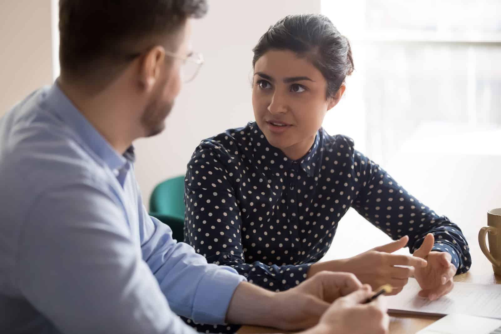 un couple en colère assis à une table et parler