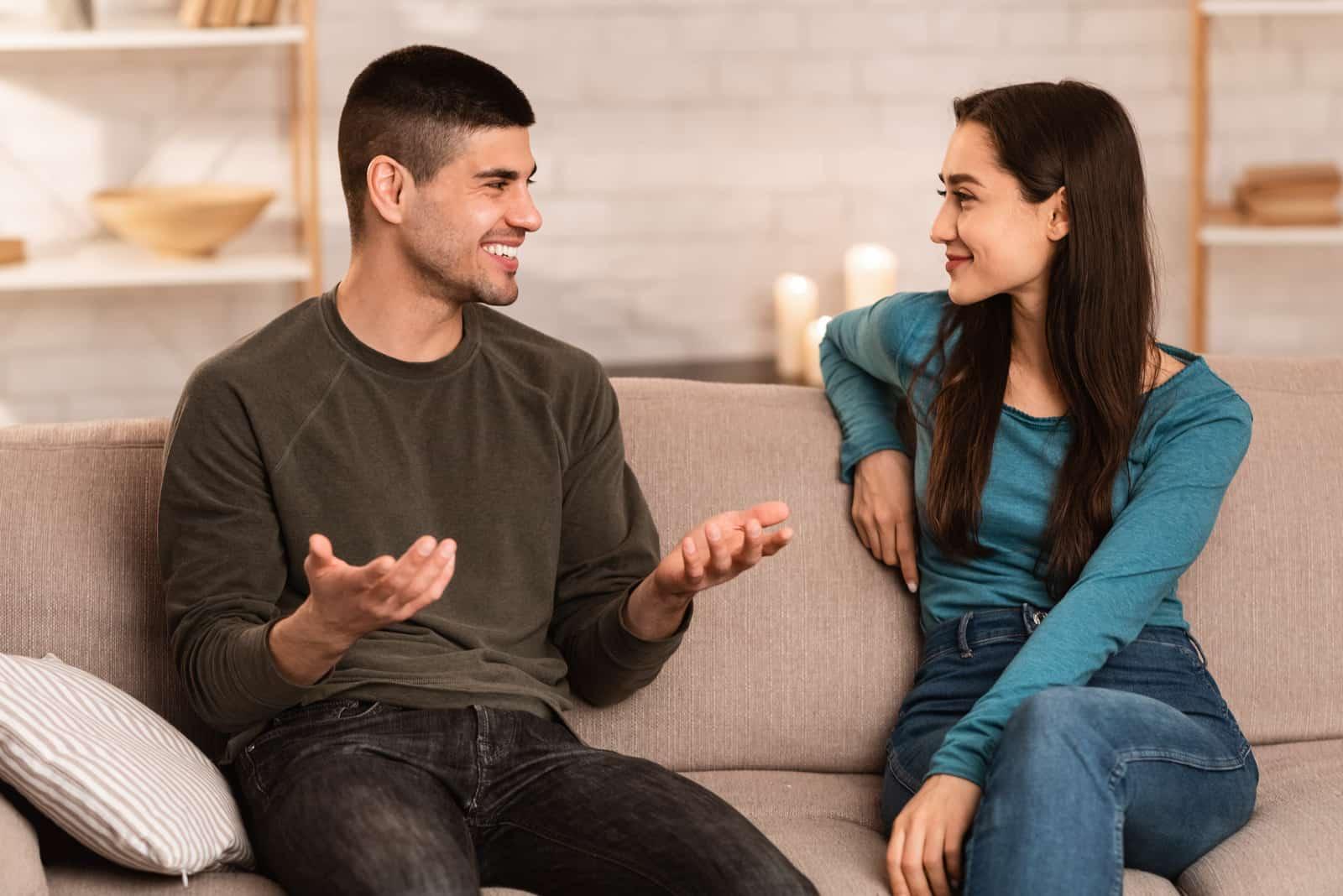 un couple souriant assis sur le canapé et parler