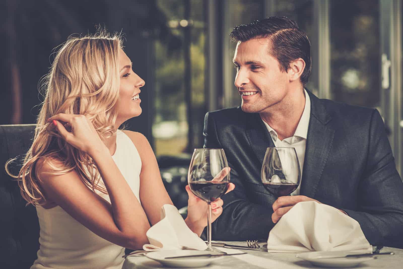 un couple souriant est assis et sourit en buvant du vin