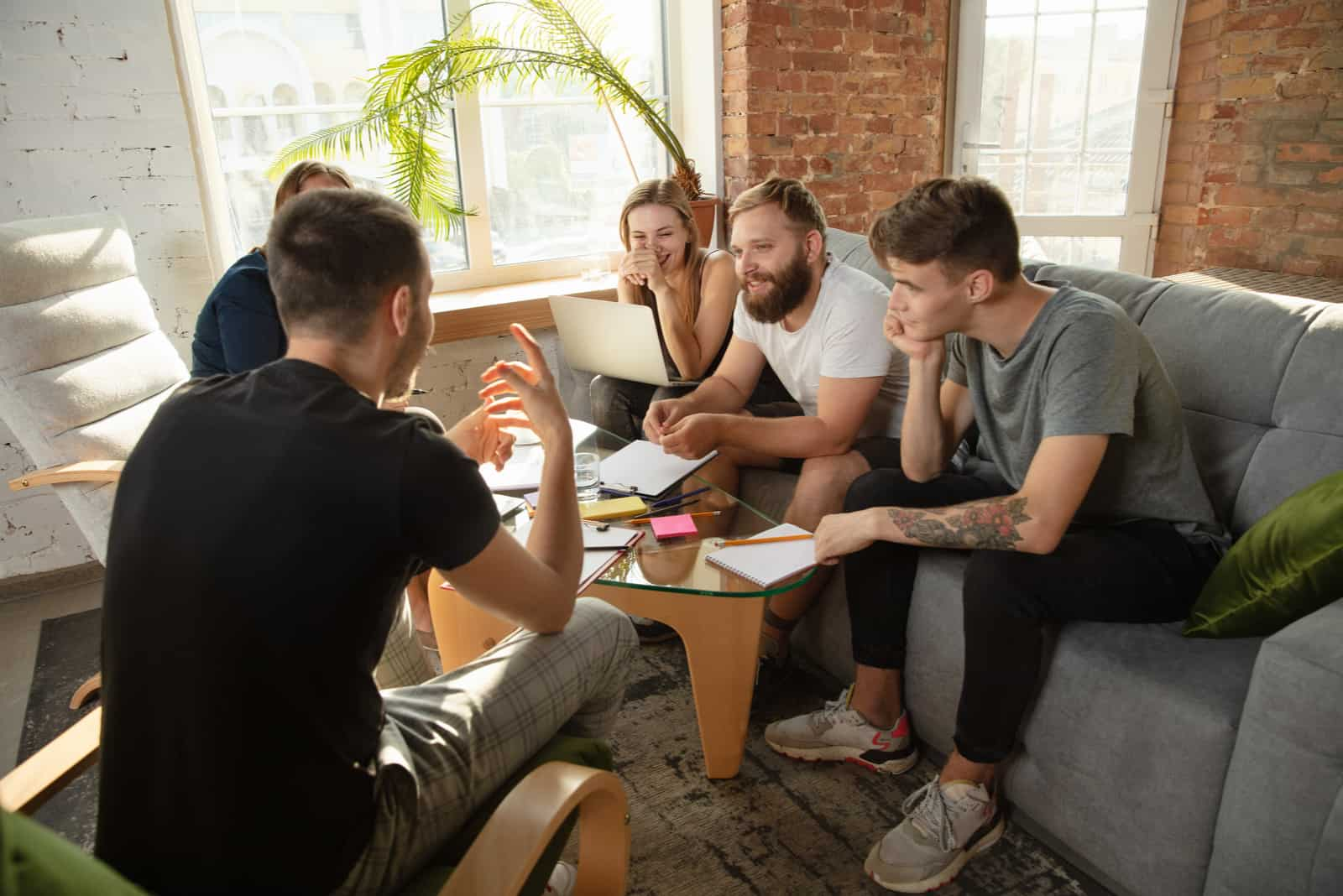 un groupe d'amis assis sur un canapé à une table
