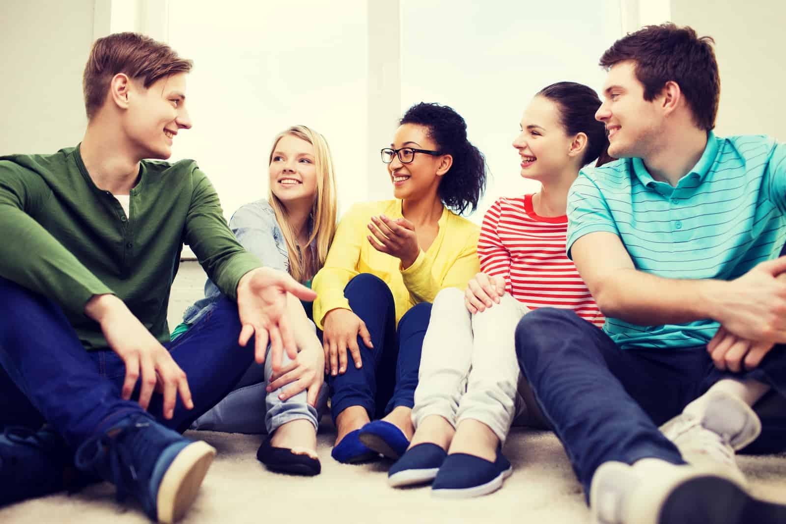un groupe d'amis est assis par terre et rit
