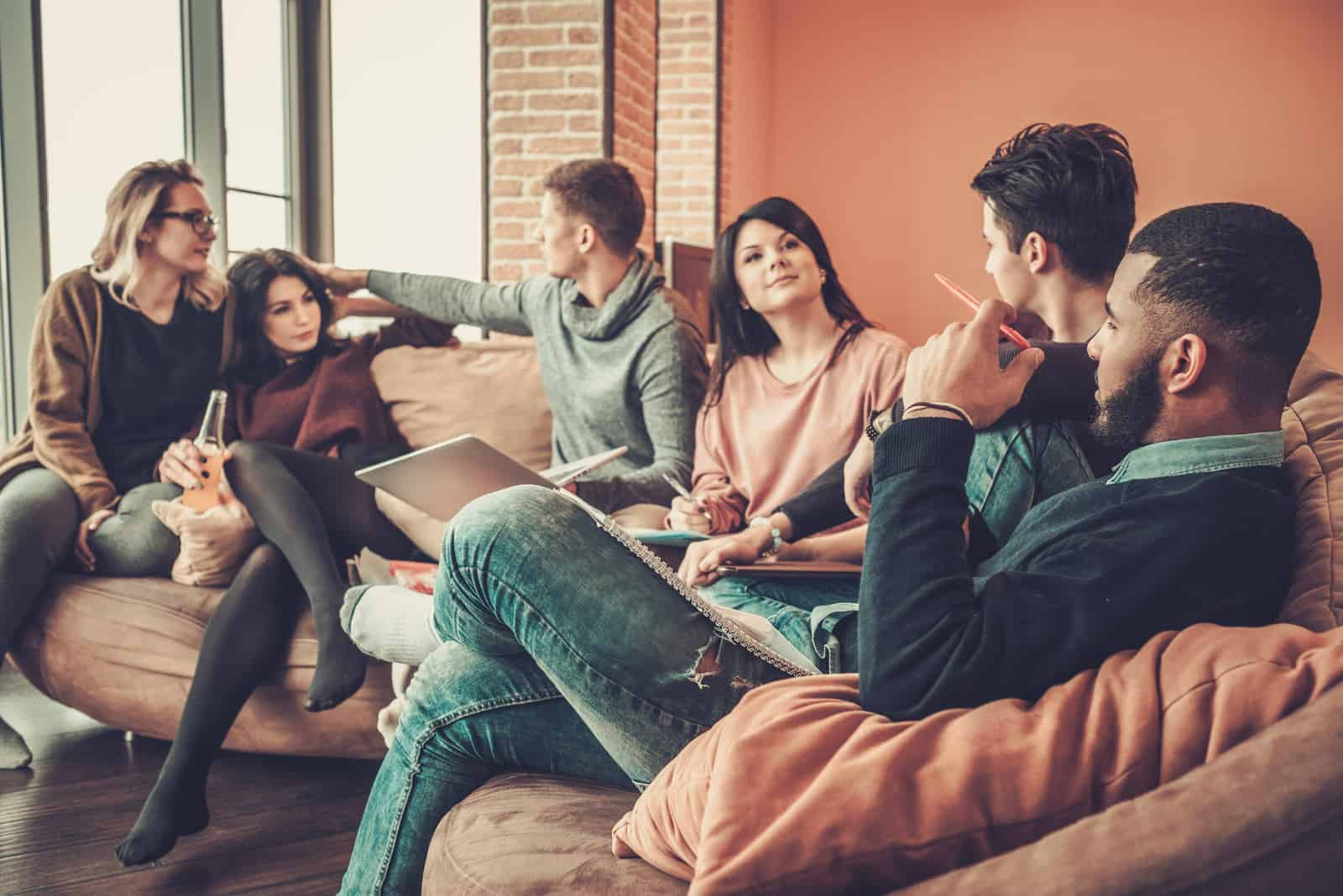 un groupe d'amis est assis sur le canapé de la maison et parle