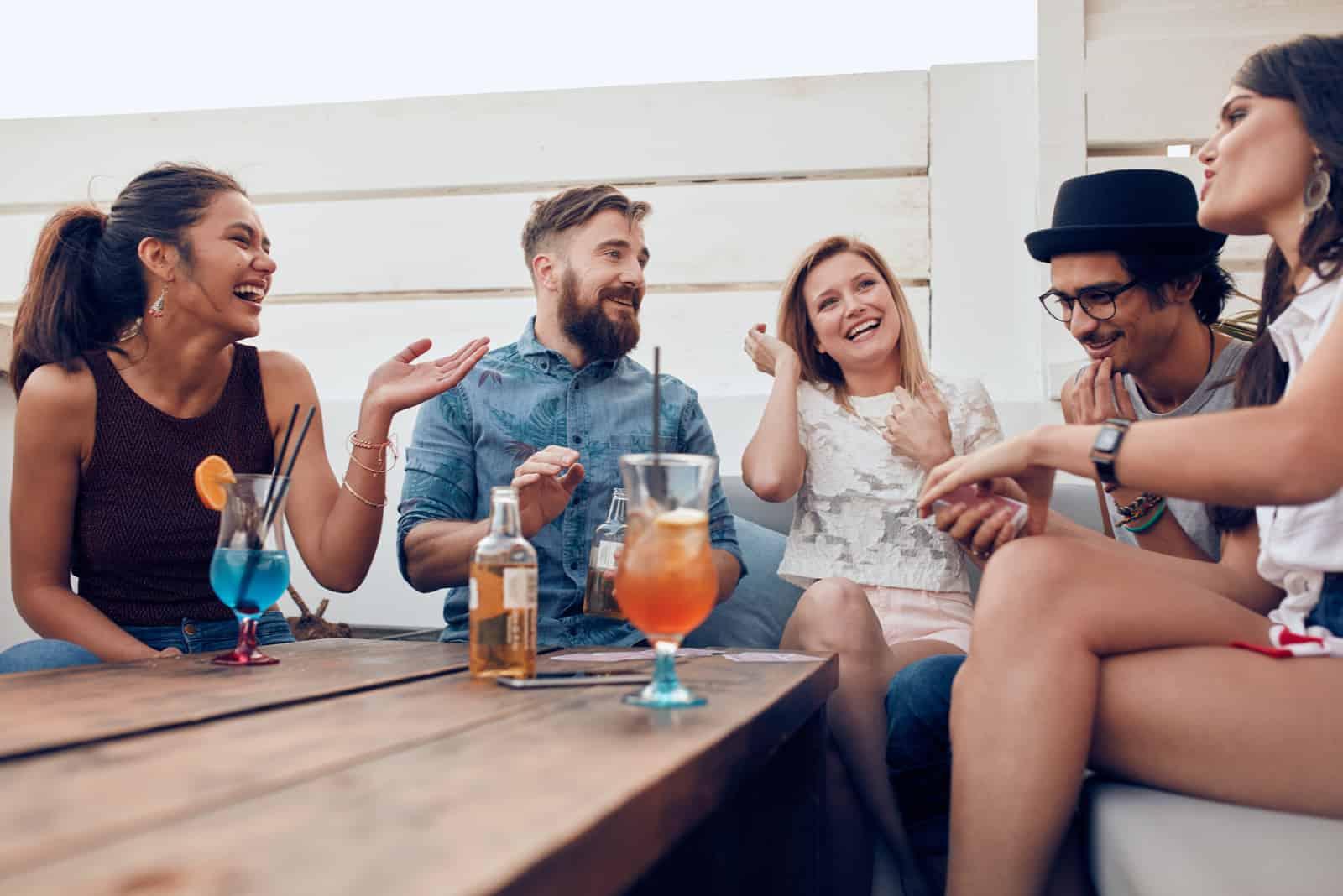 un groupe d'amis rient alors qu'ils sont assis en plein air et parlent