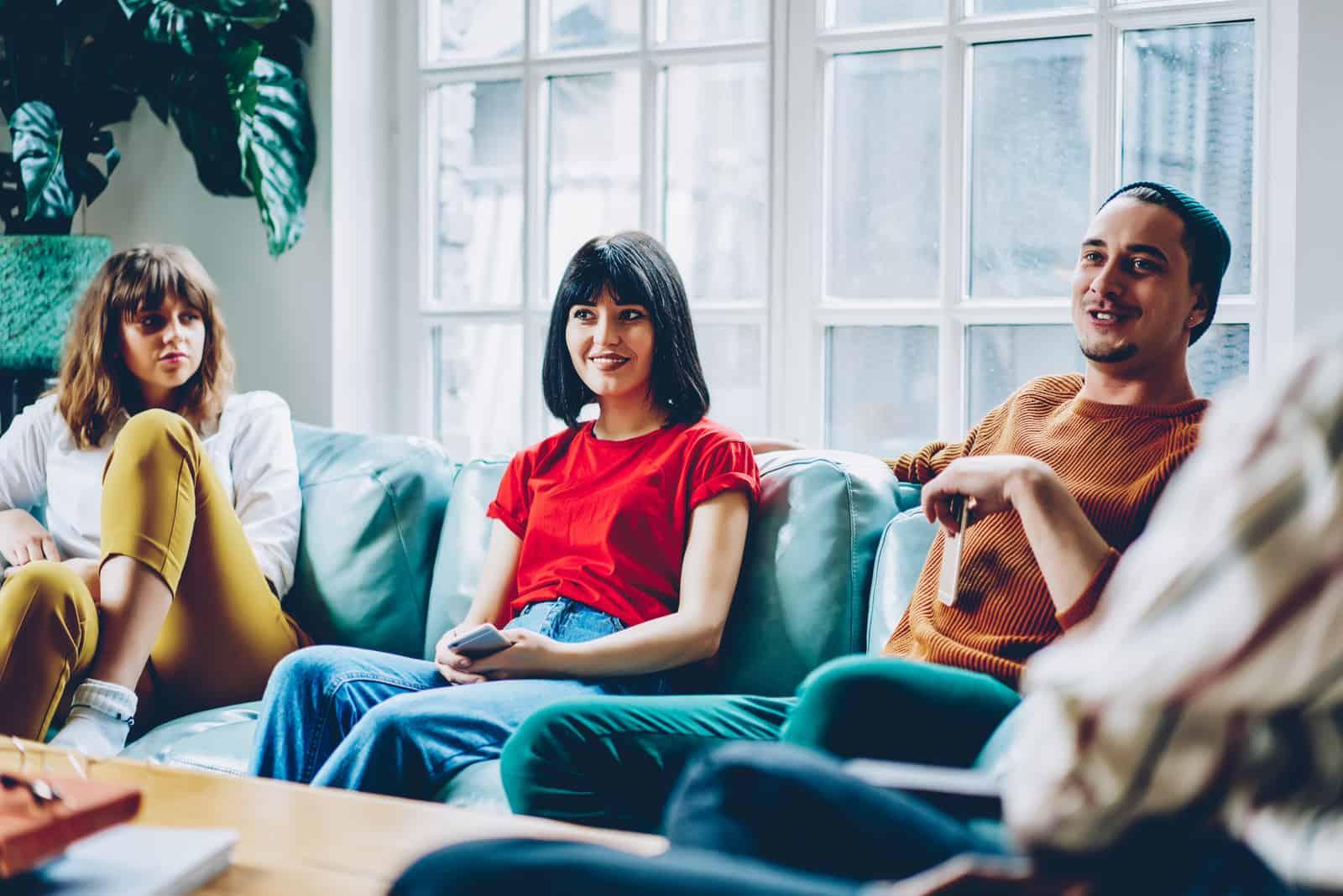 un groupe d'amis s'assied sur le canapé et parle