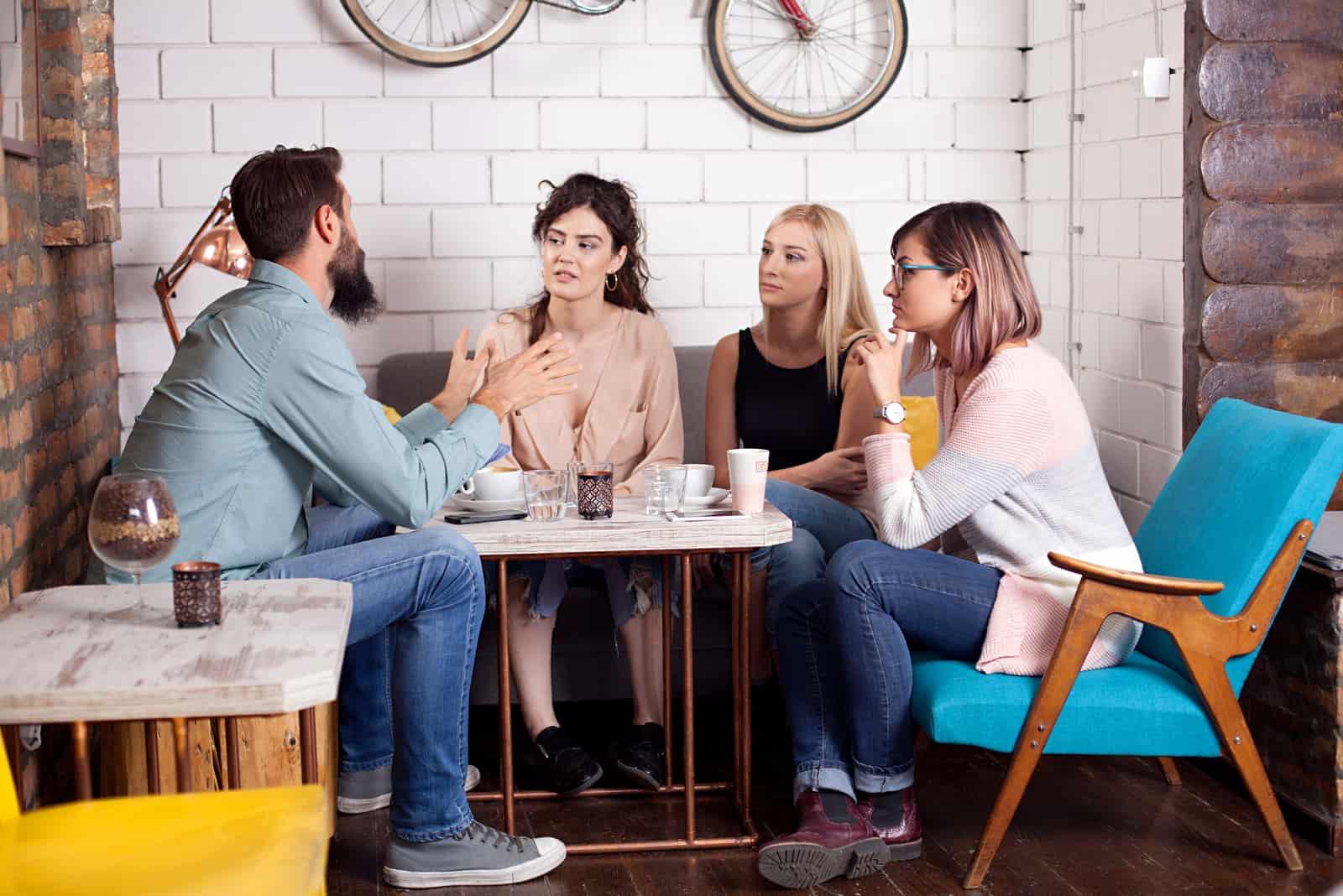 un homme avec trois femmes est assis à une table