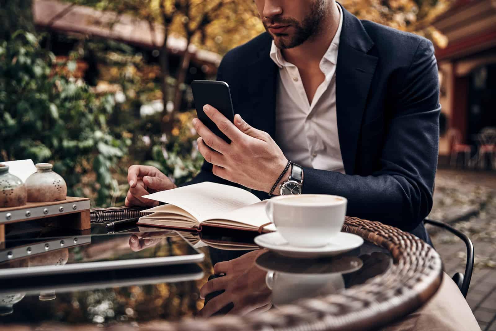 un homme est assis à une table tenant un téléphone à la main