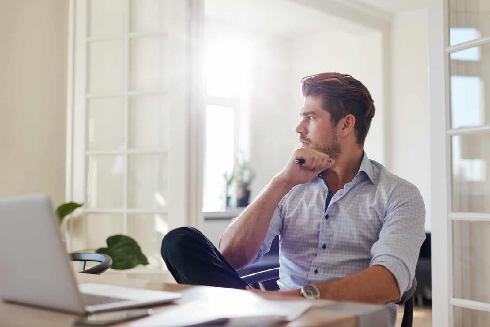un homme est assis pensivement au bureau