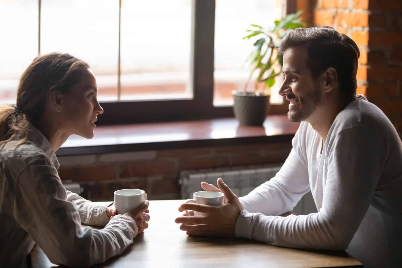 un homme et une femme assis à une table tenant une tasse de café à la main et parler