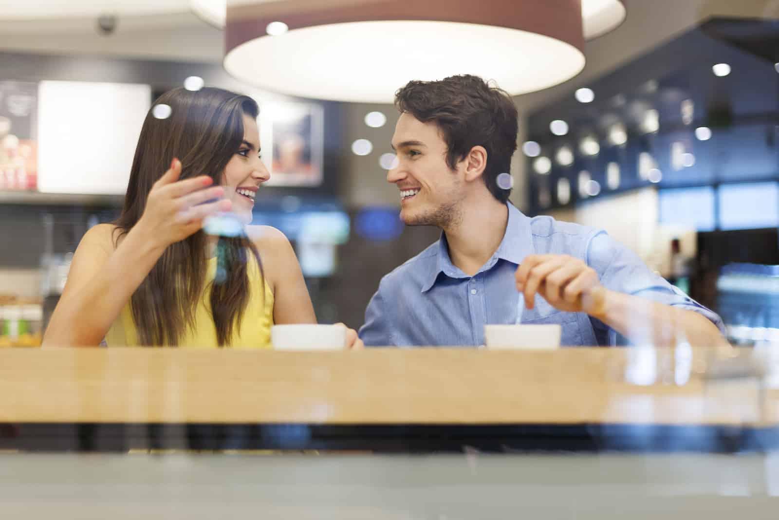 un homme et une femme dans un café sont assis en train de boire du café et de rire