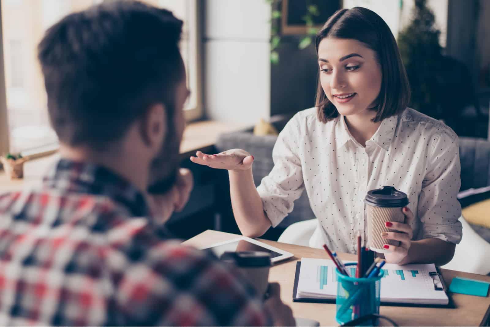 un homme et une femme s'assoient à une table et parlent