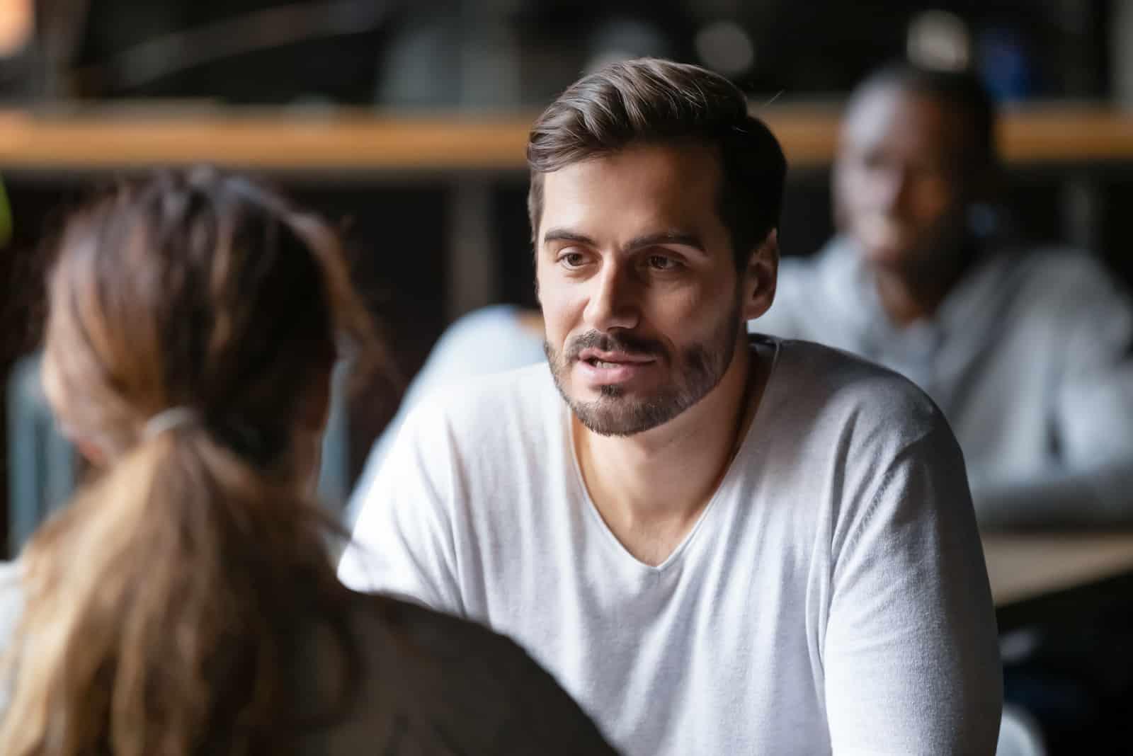 un homme et une femme s'assoient dans un café à une table et parlent