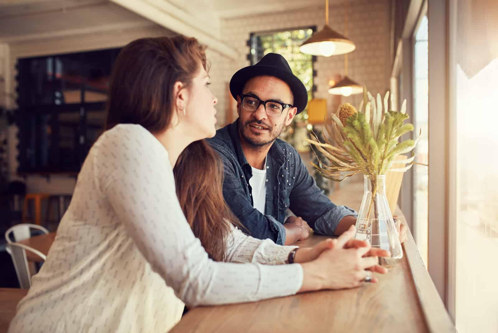 un homme et une femme s'assoient et parlent dans un café