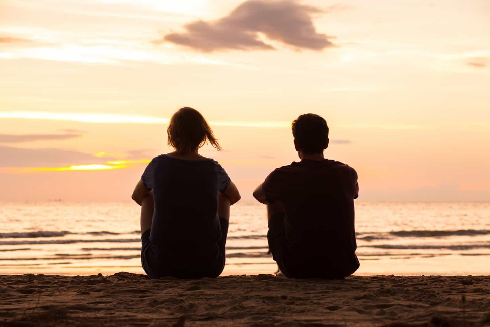 un homme et une femme s'assoient sur la plage et parlent