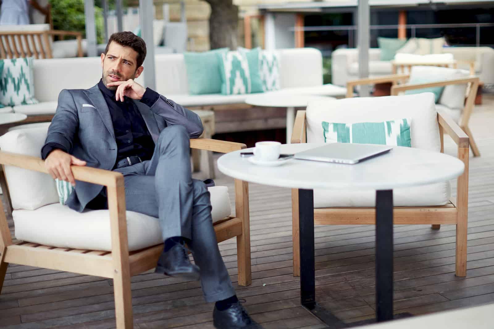 un homme imaginaire est assis à une table et regarde au loin