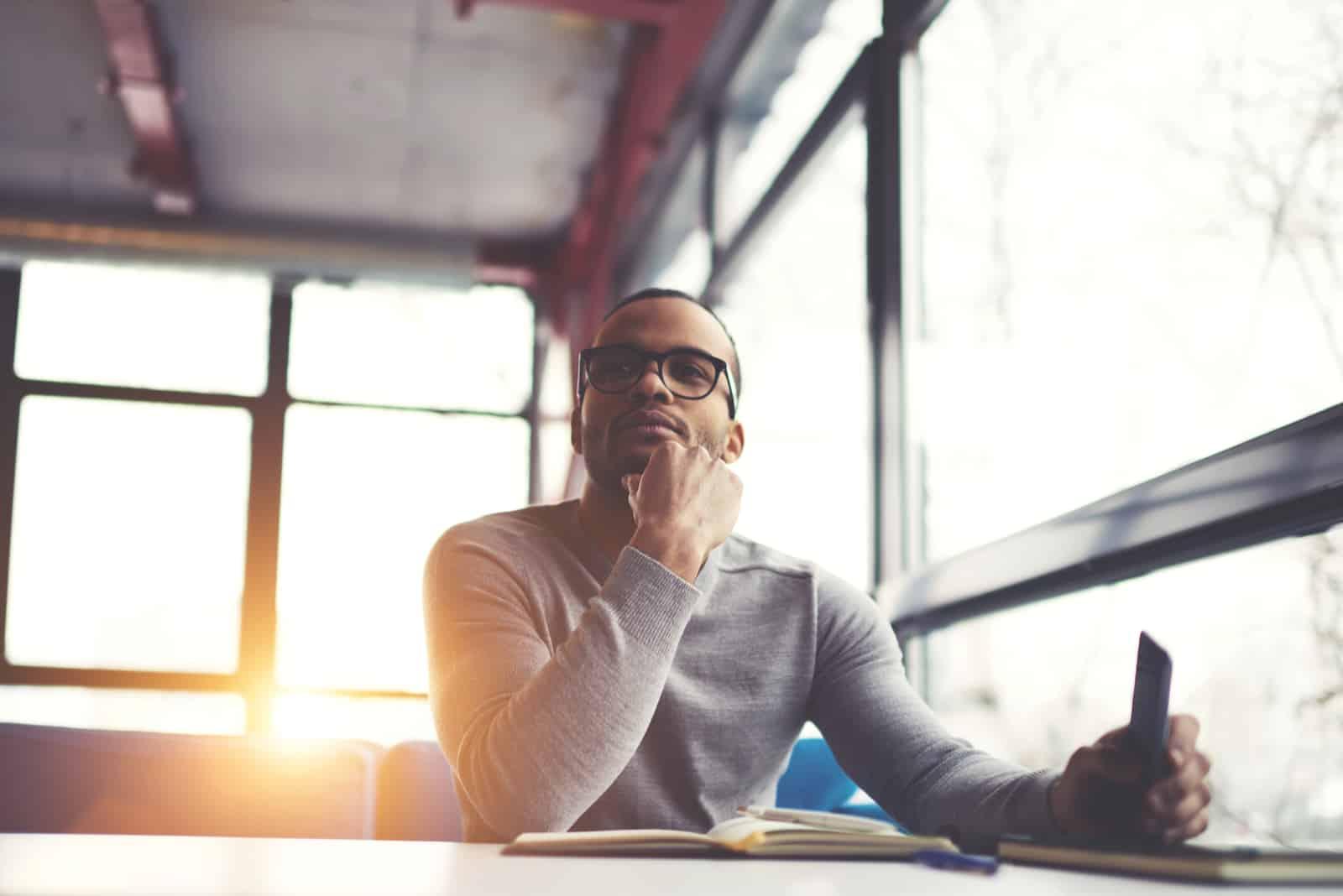 un homme imaginaire est assis à une table et tient un téléphone à la main