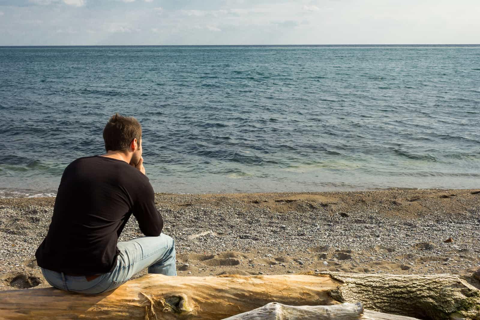 un homme imaginaire est assis sur un arbre et regarde la mer