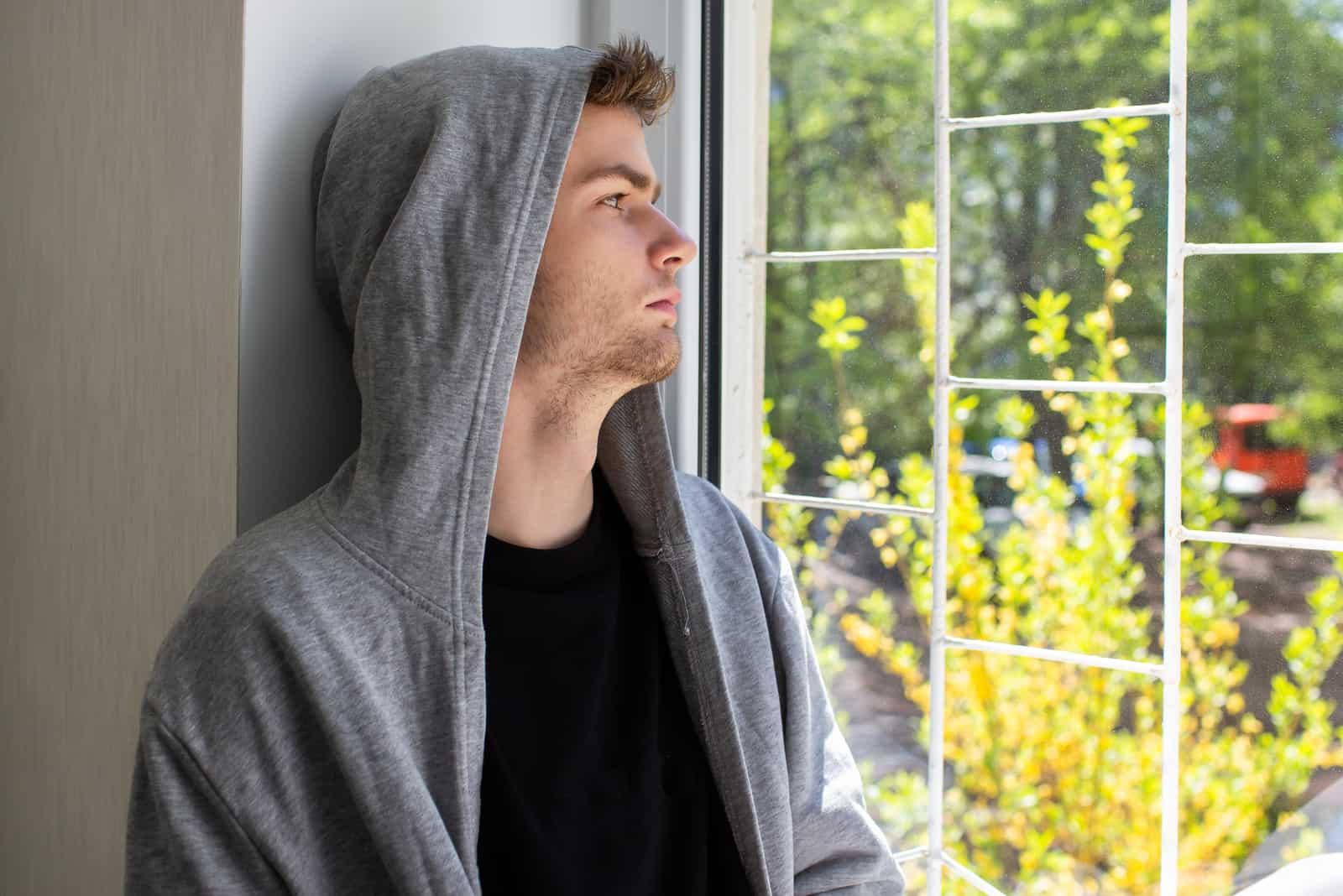 un homme imaginaire regarde par la fenêtre