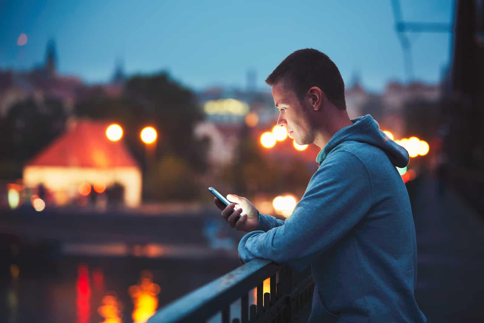 un homme imaginaire se tient près de la clôture et tient un téléphone à la main
