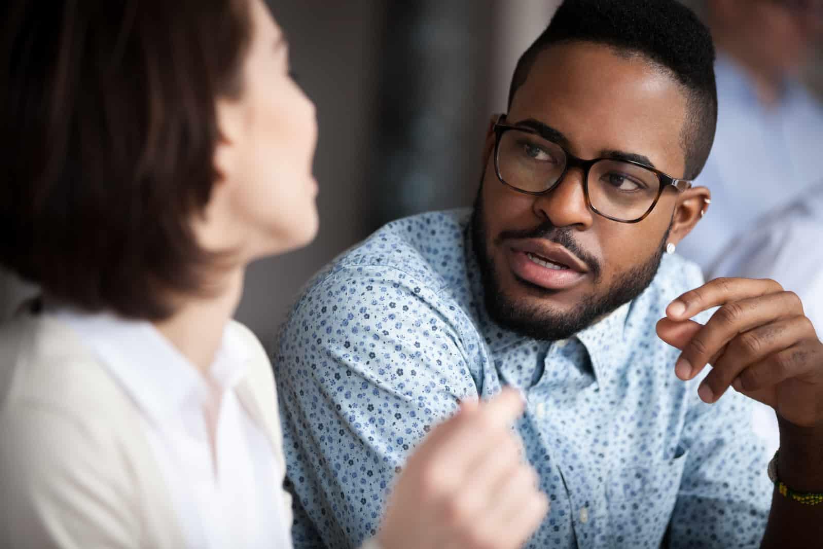 un homme noir parle à une femme