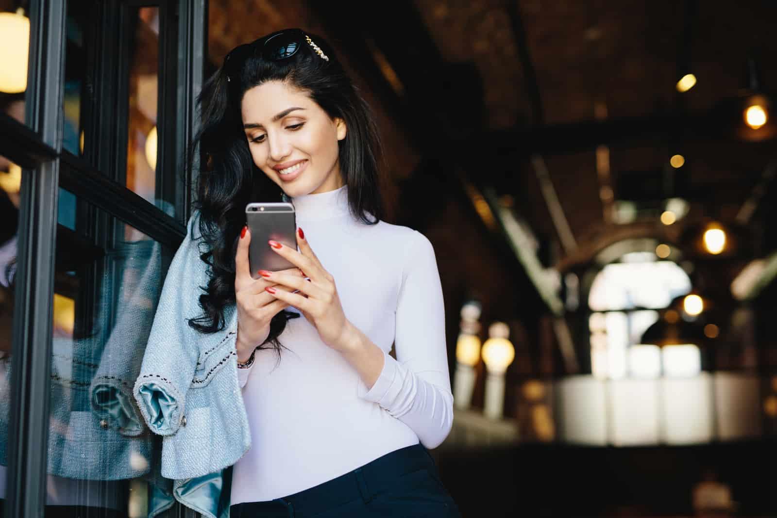 une belle femme aux cheveux noirs se dresse et des boutons sur le téléphone